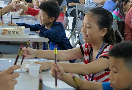 台中圳堵国小32名学童在家长的陪同下参与《悠游字在》的书法课程,学习使用毛笔写字。