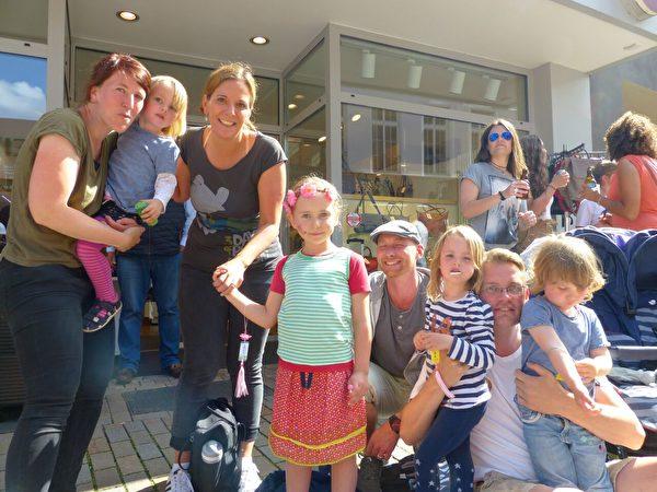 Sara女士和友人兩家合照,孩子們人手一朵蓮花。(莫凌/大紀元)