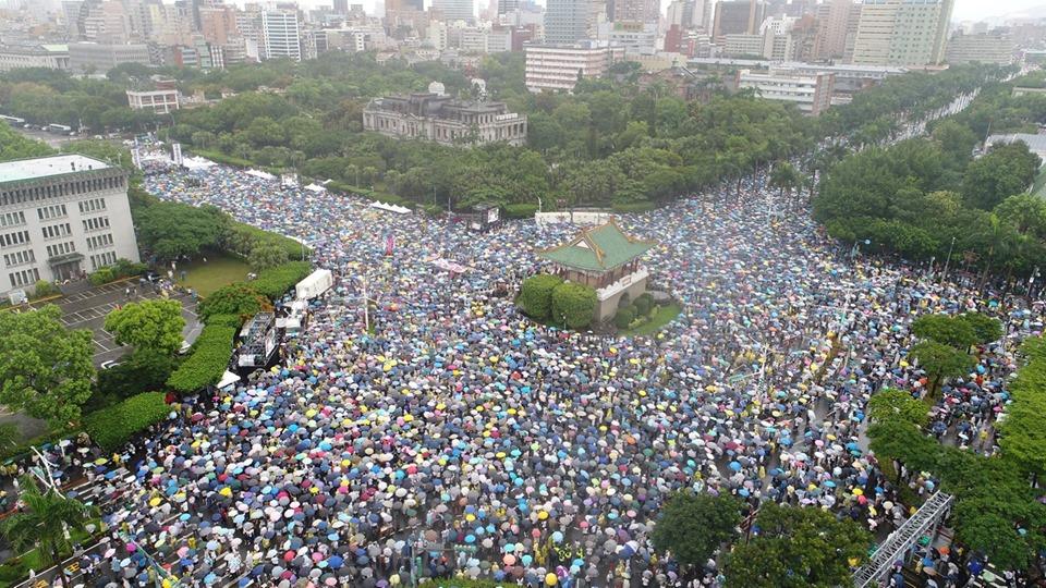 「拒絕紅色媒體、守護台灣民主」活動23日下午在總統府前凱達格蘭大道登場,大批民眾冒雨到場響應,舉出標語表達訴求。(大紀元)
