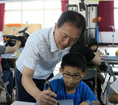 圳堵国小校长蔡宗信,在《悠游字在》的学习课程中,指导小朋友用毛笔写字。