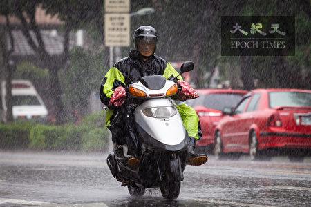 中央氣象局表示,梅雨鋒面11日凌晨鋒面進入台灣北部陸地,加上西南氣流影響,西半部須留意短時強降雨、雷擊及強陣風。圖為機車騎士穿著雨衣、雨鞋在大雨中行駛。