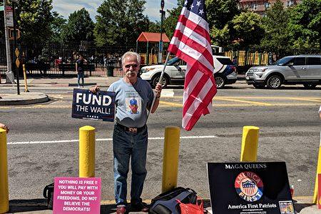 """总统川普支持者""""MAGA Queens""""组织的成员,在交流会场外手举""""Fund the wall""""标语。"""