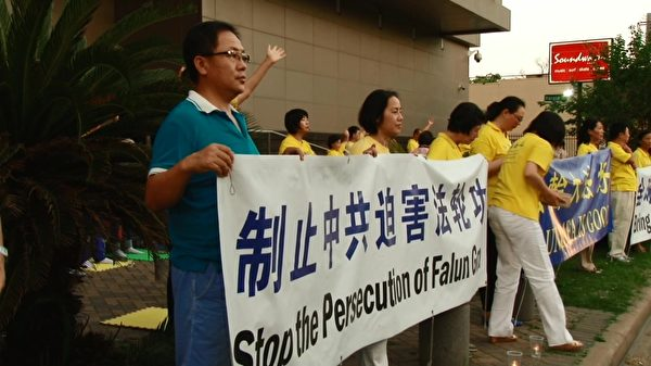 刘晓斌(左一)手持横幅,抗议中共对法轮功的迫害。(刘晓斌提供)