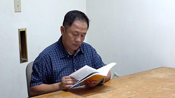 刘晓斌在阅读《转法轮》。(刘晓斌提供)