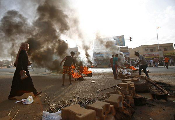 蘇丹抗議民眾焚燒輪胎來阻擋道路。(ASHRAF SHAZLY/AFP/Getty Images)