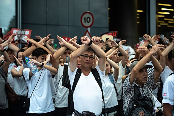 """Protesters gesture as they chant """"no extradition"""" as they rally against a controversial extradition law proposal in Hong Kong on June 9, 2019. - Huge protest crowds thronged Hong Kong on June 9 as anger swells over plans to allow extraditions to China, a proposal that has sparked the biggest public backlash against the city's pro-Beijing leadership in years. (Photo by Philip FONG / AFP) (Photo credit should read"""