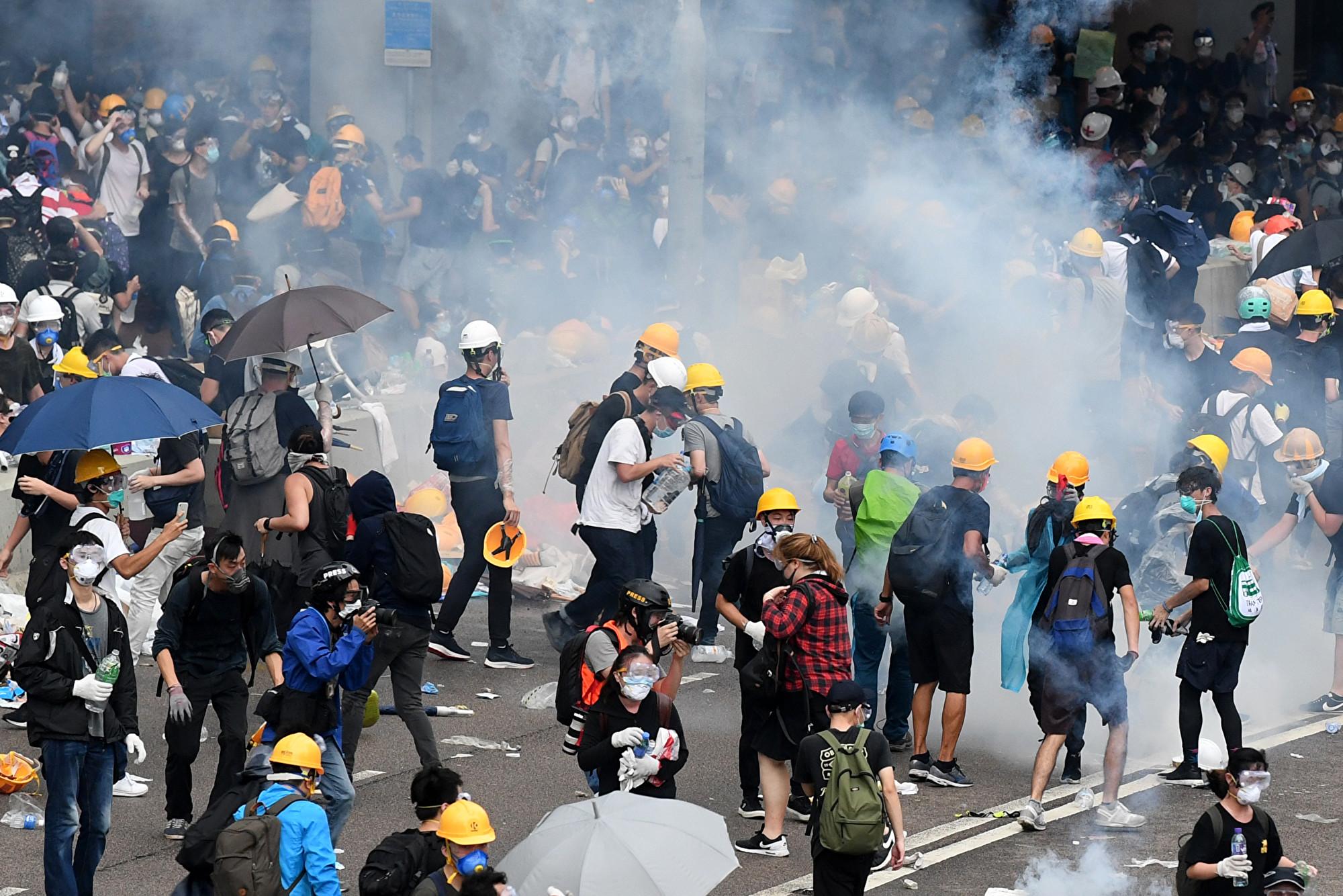 2019年6月12日,港警對手無寸鐵的群眾發射催淚煤氣與橡膠子彈,示威者以傘當盾牌抵擋。(ANTHONY WALLACE/AFP/Getty Images)