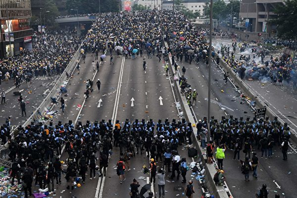 - Protesters face off with police after they fired tear gas during a rally against a controversial extradition law proposal outside the government headquarters in Hong Kong on June 12, 2019. - Violent clashes broke out in Hong Kong on June 12 as police tried to stop protesters storming the city's parliament, while tens of thousands of people blocked key arteries in a show of strength against government plans to allow extraditions to China. (Photo by Anthony WALLACE / AFP) (Photo credit should read ANTHONY WALLACE/AFP/Getty Images)