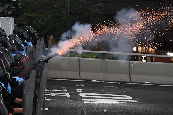A policeman fires a tear gas shell during a rally against a controversial extradition law proposal outside the government headquarters in Hong Kong on June 12, 2019. - Violent clashes broke out in Hong Kong on June 12 as police tried to stop protesters storming the city's parliament, while tens of thousands of people blocked key arteries in a show of strength against government plans to allow extraditions to China. (Photo by Anthony WALLACE / AFP) (Photo credit should read