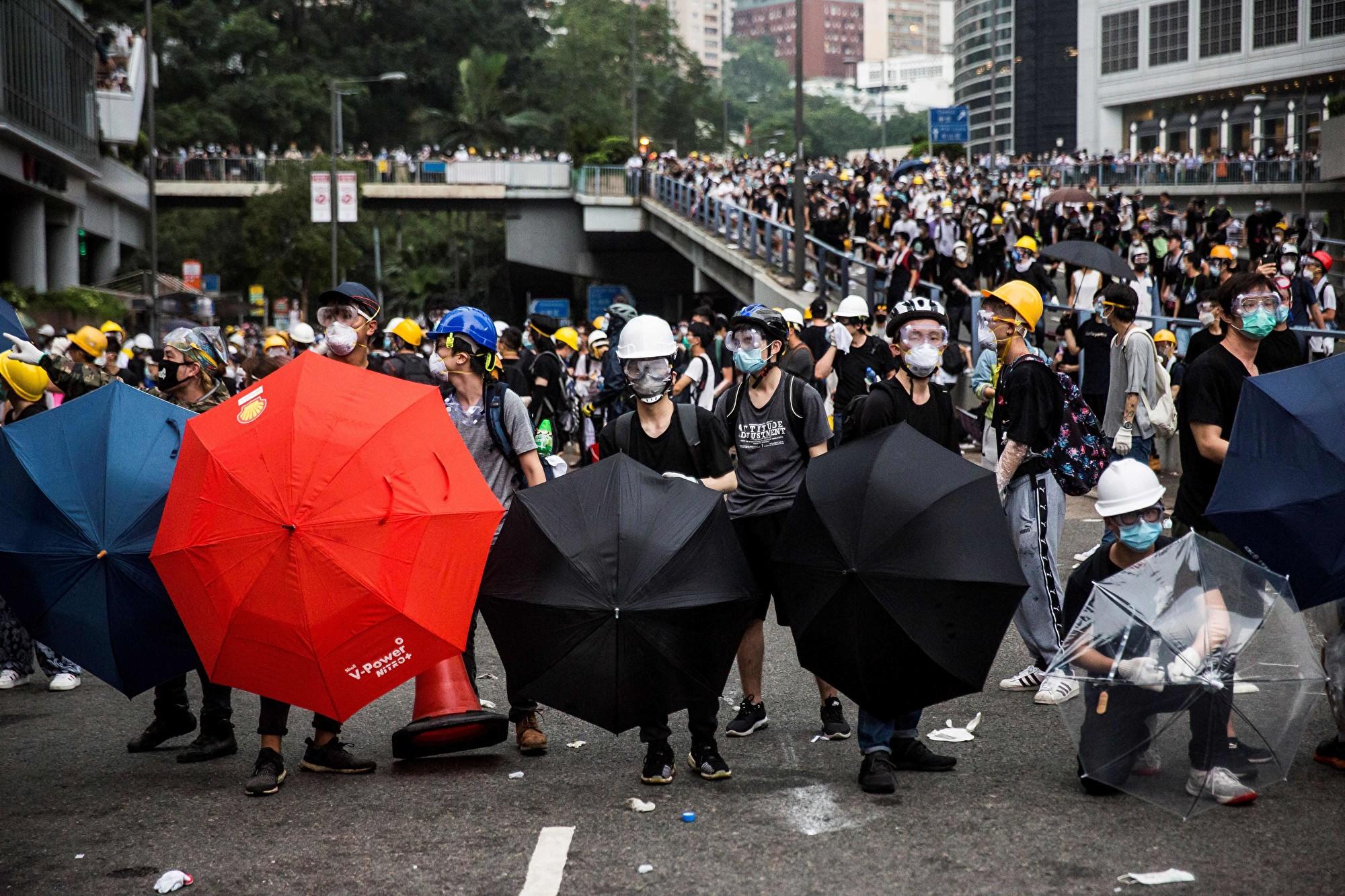 2019年6月12日,香港民眾戴著口罩拿著雨傘走上街頭,抗議香港政府不顧反對聲浪,預定二讀《逃犯條例》。(ISAAC LAWRENCE/AFP/Getty Images)