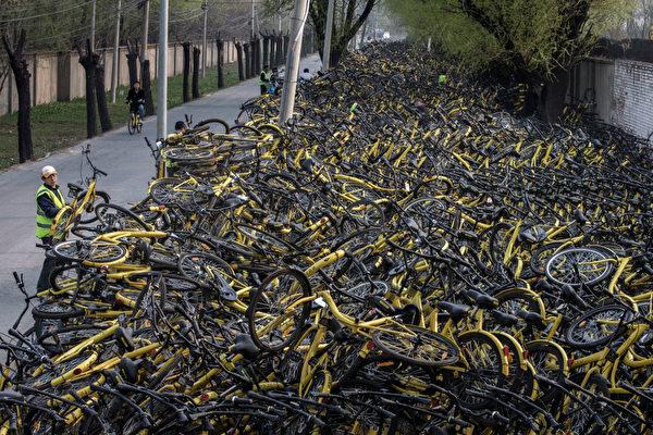 北京街頭的一名工人把一輛損壞的ofo小黃車放在一個臨時修理場所,那裏有成千上萬被廢棄的ofo共享單車。(Kevin Frayer/Getty Images)