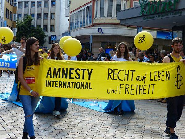 國際特赦本地高校組的Lana Eisele(左前)帶領同學以藝術形式呼籲自由與人權。(莫凌/大紀元)