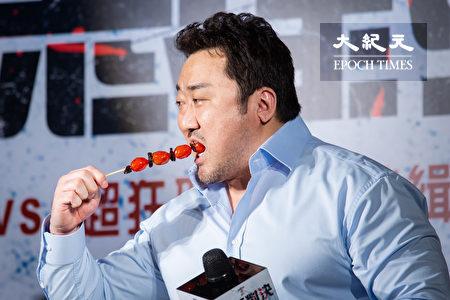 韓國男星「地表最強大叔」馬東石18日登台宣傳新片,現場品嘗台灣小吃糖葫蘆。