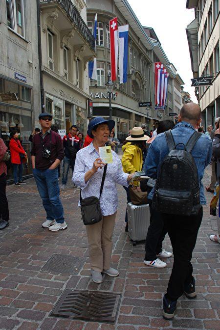 2019年6月,在盧塞恩景點,79歲的潘淑珍給中國遊客們講真相。(潘淑珍提供)