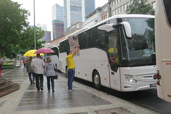 一位法輪功學員冒雨向中國遊客乘坐的大巴展示展板,希望他們多了解一些真相。(余平/大紀元)