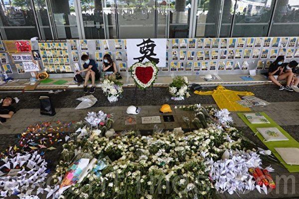 市民在立法會外為因「反送中」墜樓死亡的示威者,獻上鮮花、紙花和紙鶴。(余鋼/大紀元)