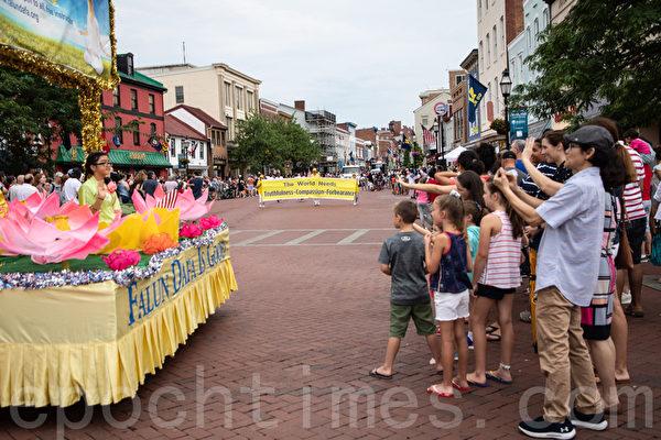 7月4日,法輪功學員參加馬里蘭州安納普裏斯(Annapolis)獨立日遊行,與民眾互動。(林樂予/大紀元)