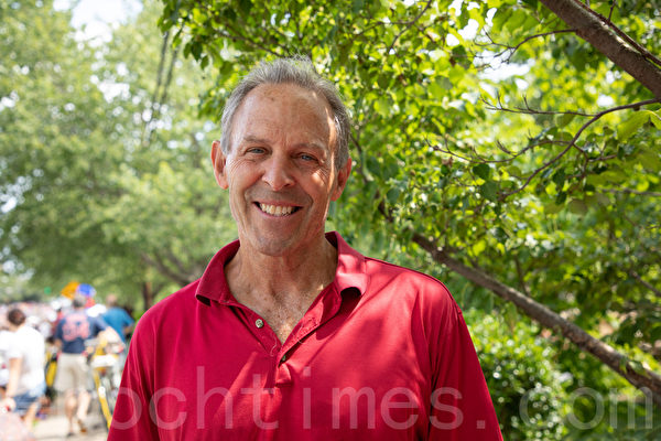 醫生吉姆·鮑(Jim Baugh)每年都來觀看費爾法克斯獨立日遊行,他很喜歡法輪功的花車,站在路邊熱情地招手。(林樂予/大紀元)