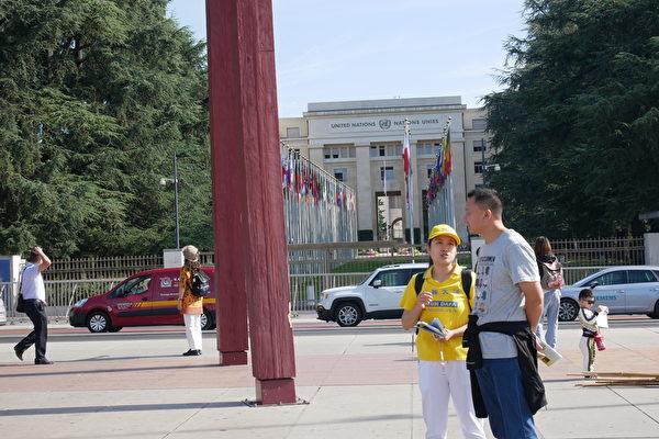 7月17日,中國遊客真相展板前,傾聽法輪功學員的講解。(張妮/大紀元)