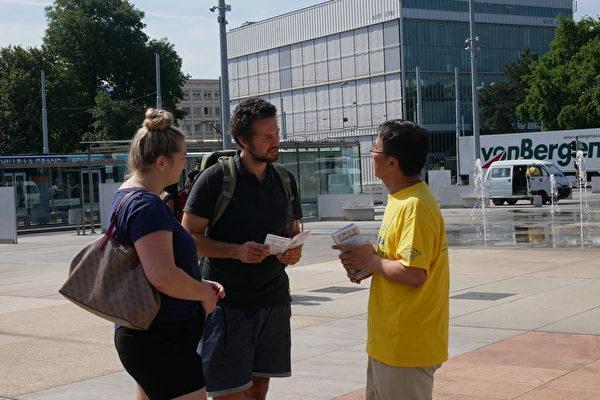 7月17日,國際遊客在向法輪功學員了解真相。(張妮/大紀元)