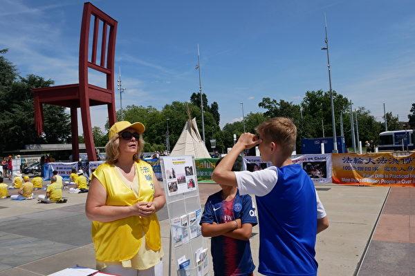 7月17日,12歲的瑞士男孩Sacha和他的朋友Eddy好奇地主動向法輪功學員詢問,他們神色嚴肅地聽法輪功學員講述在中國發生的故事。(張妮/大紀元)