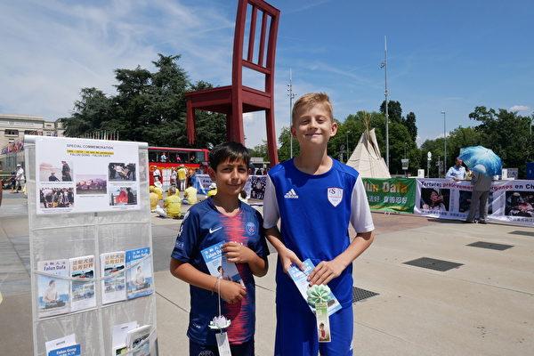 12歲的瑞士男孩Sacha和他的朋友Eddy拿了真相傳單後,在展板前留影。(張妮/大紀元)