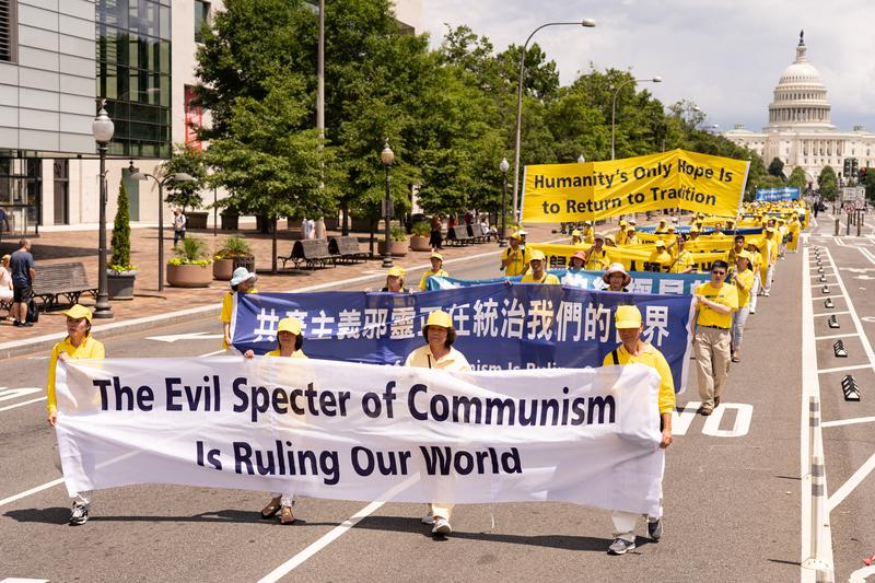 2019年7月18日,近二千名法輪功學員聚集在華盛頓DC舉行法輪功反迫害20周年大遊行。圖為法輪功學員以橫幅告訴世人「The Evil Specter of Communism is Ruling Our World 共產主義魔鬼正在統治我們的世界」。(戴兵/大紀元)