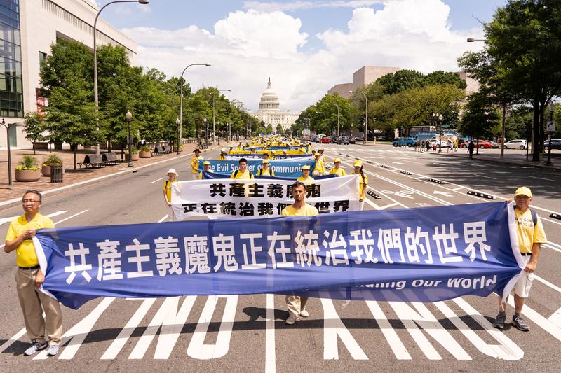 2019年7月18日,近二千名法輪功學員聚集在華盛頓DC舉行法輪功反迫害20周年大遊行。圖為法輪功學員以橫幅告訴世人「共產主義魔鬼正在統治我們的世界」。(戴兵/大紀元)
