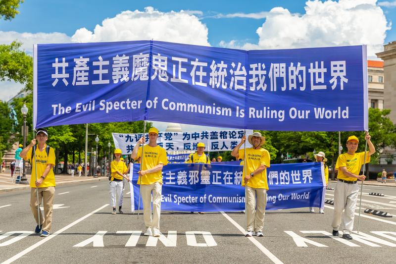 2019年7月18日,近二千名法輪功學員聚集在華盛頓DC舉行法輪功反迫害20周年大遊行。圖為法輪功學員以橫幅告訴世人「共產主義魔鬼正在統治我們的世界」。(Mark Zou/大紀元)