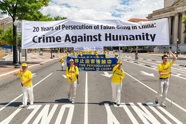 2019年7月18日,近二千名法輪功學員在華盛頓DC舉行法輪功反迫害20周年大遊行。圖為法輪功學員持「20 years of persecution of Falun Gong in china:Crime Against Humanity」的橫幅告訴世人中共迫害法輪功是反人類罪。(Mark Zou/大紀元)
