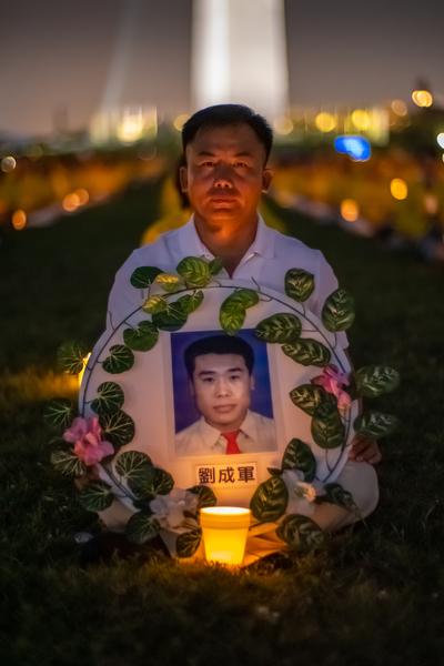 7月18日晚,原籍長春的法輪功學員王建民在華盛頓DC燭光夜悼活動中手持「3·05」英烈劉成軍的遺像。(Mark Zou/大紀元)