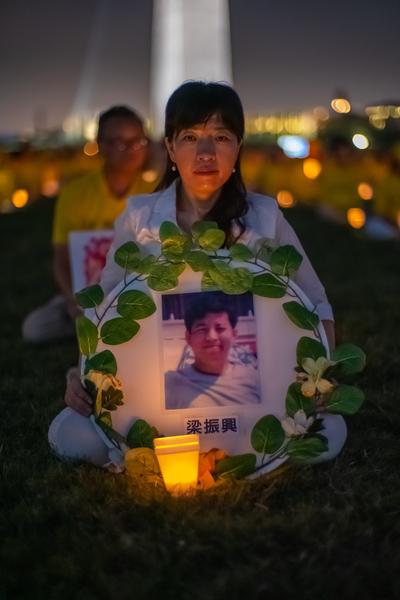 7月18日晚,原籍長春的法輪功學員蘭麗華在華盛頓DC燭光夜悼活動中手持「3·05」英烈梁振興的遺像。(Mark Zou/大紀元)