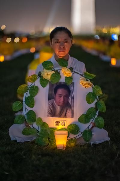 7月18日晚,原籍長春的法輪功學員陳敬宇在華盛頓DC燭光夜悼活動中手持「3·05」英烈雷明的遺像。(Mark Zou/大紀元)