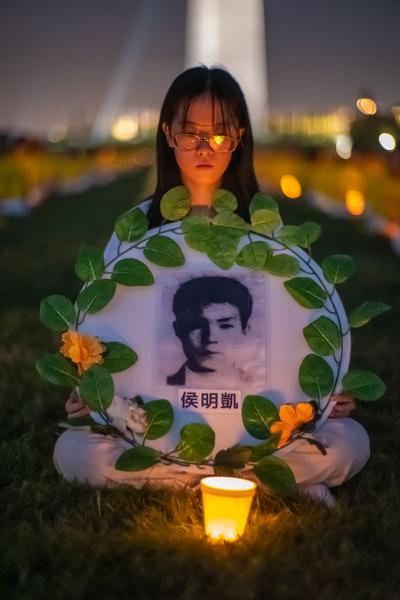 7月18日晚,原籍長春的法輪功學員張華旗在華盛頓DC燭光夜悼活動中手持「3·05」英烈侯明凱的遺像。(Mark Zou/大紀元)