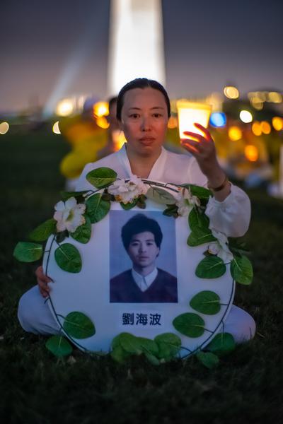 7月18日晚,原籍長春的法輪功學員朱雅莉在華盛頓DC燭光夜悼活動中手持「3·05」英烈劉海波的遺像。(Mark Zou/大紀元)