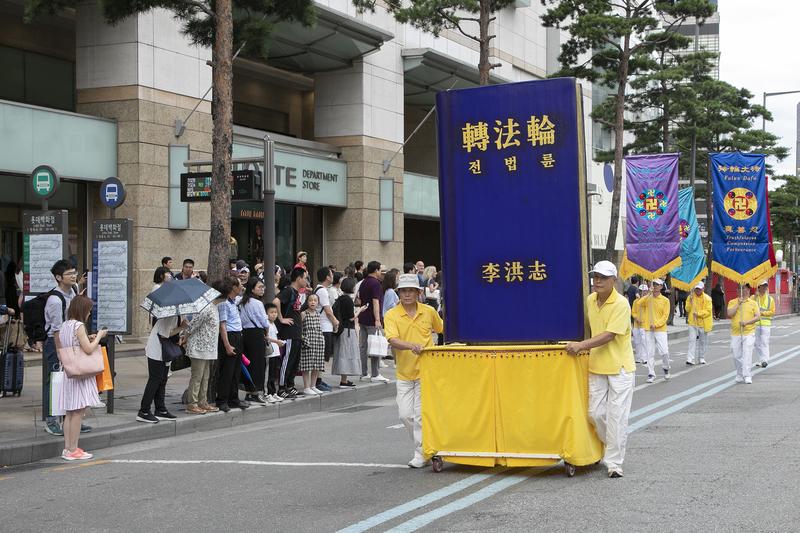 2019年7月20日,南韓法輪功學員在首爾舉行反迫害20年遊行,傳播法輪功真相呼籲中共停止迫害,許多民眾駐足觀看。圖為轉法輪大型書模。(全景林/大紀元)