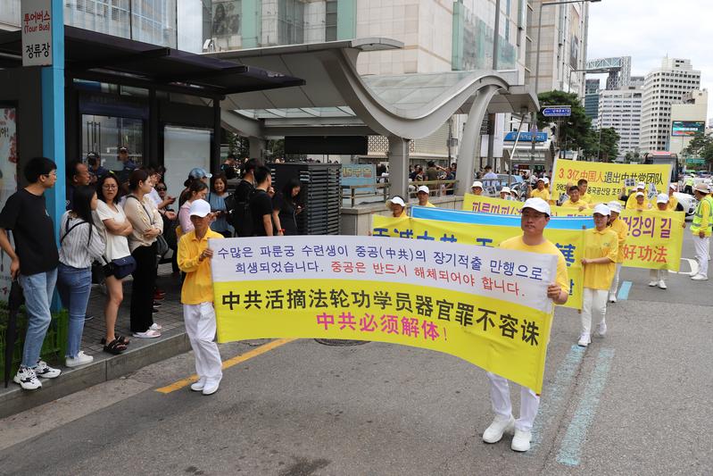 2019年7月20日,南韓法輪功學員在首爾舉行反迫害20年遊行,傳播法輪功真相呼籲中共停止迫害。圖為法輪功學員持「中共活摘法輪功學員器官罪不容誅 中共必須解體」的橫幅告訴人們真相。(金國煥)