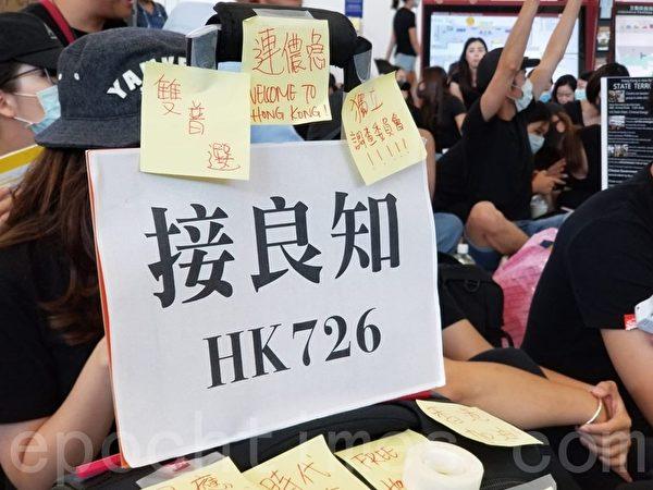 2019年7月26日,香港一群航空界職員在香港機場的接機大廳舉行集會抗議。圖為抗議人士在接機處以展板告訴民眾「接良知 HK726」。(宋碧龍/大紀元)