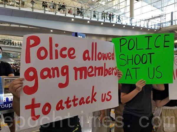 7月26日,超過2500名香港航空界職員在香港國際機場接機大堂表達訴求,有英語標語寫道:「警察允許幫派分子襲擊我們」,「警察向我們開槍」。(宋碧龍/大紀元)