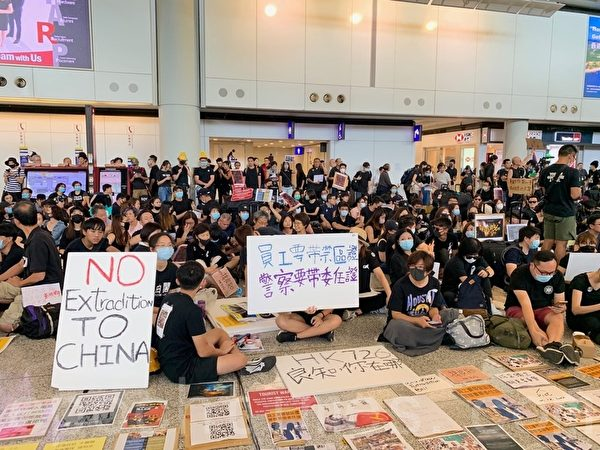 2019年7月26日,香港一群航空界職員在香港機場的接機大廳舉行集會抗議,他們以派發傳單和手舉標語等方式向入境民眾反映香港人反送中的訴求。(李逸/大紀元)