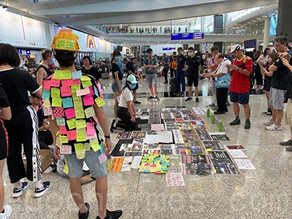 2019年7月26日,香港一群航空界職員在香港機場的接機大廳舉行集會抗議。圖為一名男士化身「連儂人」,全身貼了許多市民寫的便利貼。(李逸/大紀元)