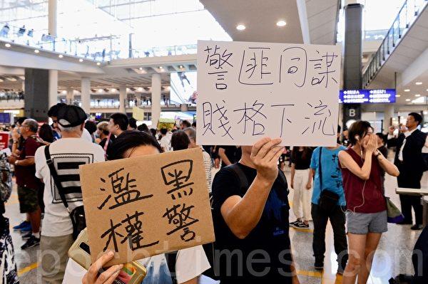 2019年7月26日,香港一群航空界職員在香港機場的接機大廳舉行集會抗議。圖為抗議人士以展板告訴民眾「黑警濫權」、「警匪同謀 賤格下流」。(宋碧龍/大紀元)