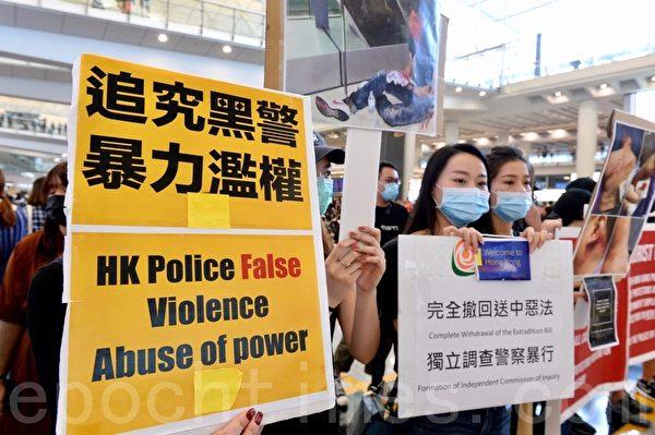 2019年7月26日,香港一群航空界職員在香港機場的接機大廳舉行集會抗議。圖為抗議人士以展板表達「追究黑警暴力濫權」、「完全撤回送中惡法 獨立調查警察暴行」的訴求。(宋碧龍/大紀元)