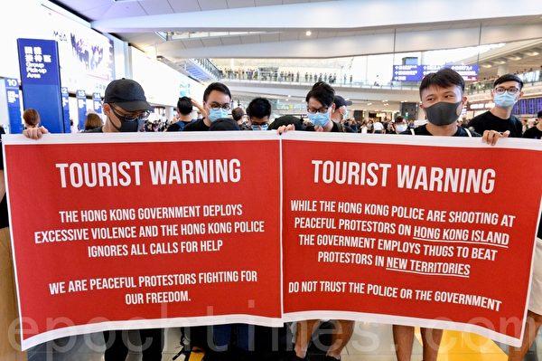 2019年7月26日,香港一群航空界職員在香港機場的接機大廳舉行集會抗議。圖為抗議人士以展板告訴旅客香港出現紅色旅遊警戒。(宋碧龍/大紀元)