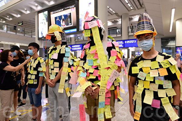2019年7月26日,香港一群航空界職員在香港機場的接機大廳舉行集會抗議。圖為幾位男士化身「連儂人」,全身貼滿市民寫的便利貼。(宋碧龍/大紀元)