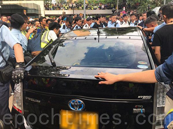 7月28日,一輛黑色私家車在終審法院外被市民包圍,現場消息指市民發現車上有警員,其後私家車由警察護送離開,大量市民尾隨車輛衝出馬路。(林怡/大紀元)