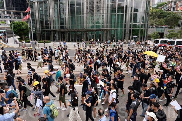 7月28日,遊行隊伍經過長江集團中心。(宋碧龍/大紀元)