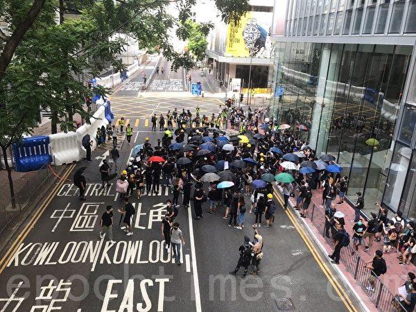 7月28日,在灣仔警察總部外,也有一批示威者開始聚集,他們打開雨傘圍在一起商討。(林怡/大紀元)