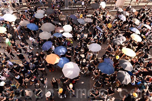 7月28日,在灣仔警察總部外,也有一批示威者開始聚集,他們打開雨傘圍在一起商討。(宋碧龍/大紀元)