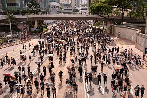7月28日,遊行隊伍經過警署附近、宜發大廈前。(宋碧龍/大紀元)